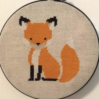 Cross stitched orange fox in black embroidery hoop with cream background